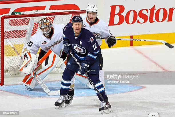 Goaltender Viktor Fasth and Hampus Lindholm of the Anaheim Ducks look around a screen set by Olli Jokinen of the Winnipeg Jets during secondperiod...