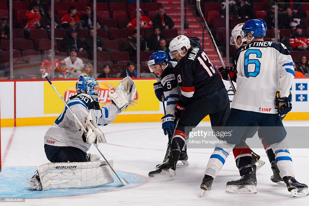 Goaltender Ville Husso #30 of Team Finland makes a glove save with teammate Aleksi Makela #5 defending against Sonny Milano #13 of Team United States during the 2015 IIHF World Junior Hockey Championship game at the Bell Centre on December 26, 2014 in Montreal, Quebec, Canada. Team United States defeated Team Finland 2-1 in a shootout.