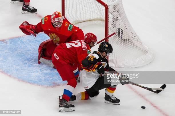 Goaltender Yaroslav Askarov and Marat Khusnutdinov of Russia skate against Enrico Henriquez Morales of Germany during the 2021 IIHF World Junior...