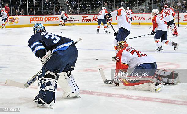 Goaltenders Al Montoya of the Winnipeg Jets and Jacob Markstrom of the Florida Panthers take part in the pregame warm up prior to NHL action at the...