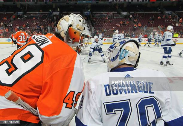 Goaltenders Alex Lyon of the Philadelphia Flyers and Louis Domingue of the Tampa Bay Lightning chat during warmups on January 25 2018 at the Wells...
