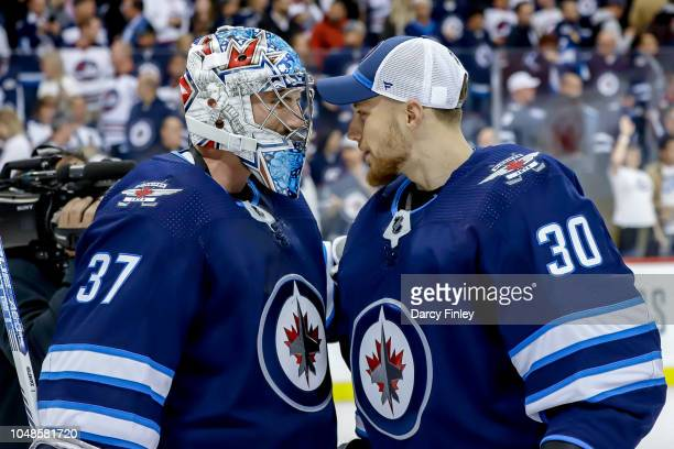 Goaltenders Connor Hellebuyck and Laurent Brossoit of the Winnipeg Jets celebrate a 21 victory over the Los Angeles Kings at the Bell MTS Place on...