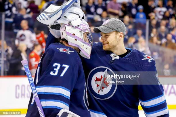 Goaltenders Connor Hellebuyck and Laurent Brossoit of the Winnipeg Jets celebrate a 65 victory over the Chicago Blackhawks at the Bell MTS Place on...