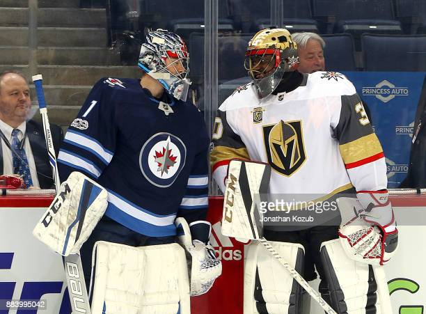Goaltenders Eric Comrie of the Winnipeg Jets and Malcolm Subban of the Vegas Golden Knights chat during the pregame warm up prior to NHL action at...