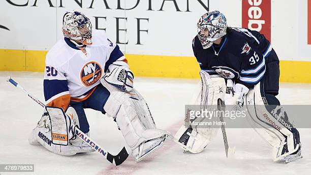 Goaltenders Evgeni Nabokov of the New York Islanders and Al Montoya of the Winnipeg Jets chat together during warmup before an NHL game at the MTS...