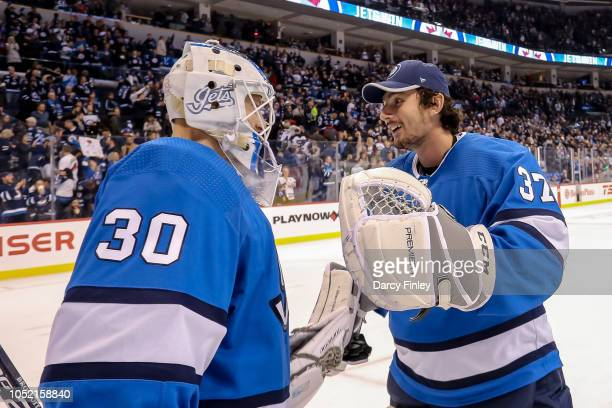 Goaltenders Laurent Brossoit and Connor Hellebuyck of the Winnipeg Jets celebrate following a 31 victory over the Carolina Hurricanes at the Bell MTS...