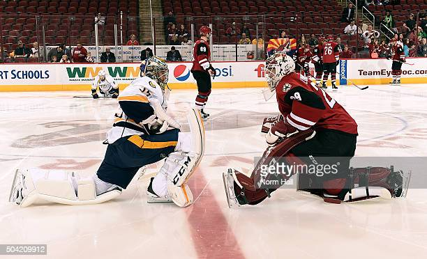 Goaltenders Pekka Rinne of the Nashville Predators and Anders Lindback of the Arizona Coyotes talk at center ice before the start of an NHL game at...