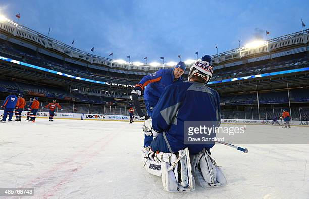 Goaltending coach Mike Dunham talks to goaltender Evgeni Nabokov of the New York Islanders during the 2014 NHL Stadium Series practice session at...