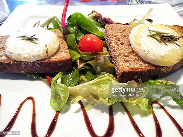 goat cheese on its bed of salad - jean marc payet stockfoto's en -beelden