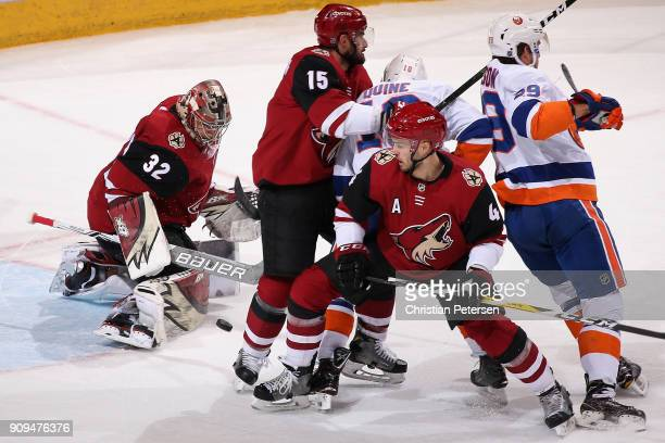 Goatlender Antti Raanta of the Arizona Coyotes makes a pad save as Niklas Hjalmarsson and Brad Richardson defend against Alan Quine and Brock Nelson...