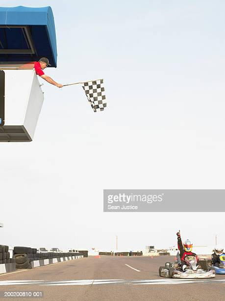 Go-cart racer crossing finish line, man waving checkered flag