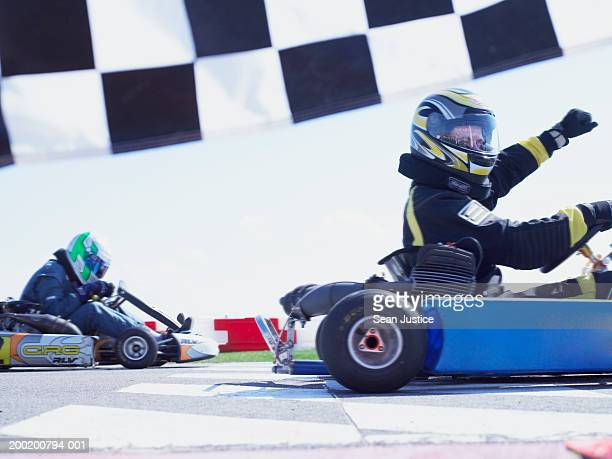 Go-cart racer crossing finish line, raising arm, side view