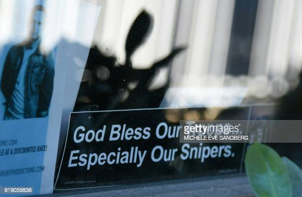 A 'God bless our troup especially our sniper' placard is seen on the window of Sunrise Tactical Supply store in Coral Springs Florida on February 16...