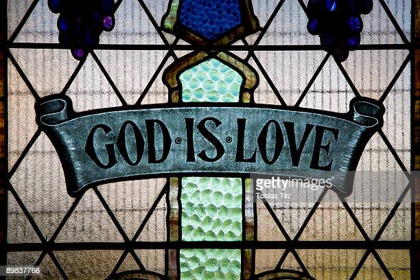 god is love written in a stained glass window - stained glass stock pictures, royalty-free photos & images
