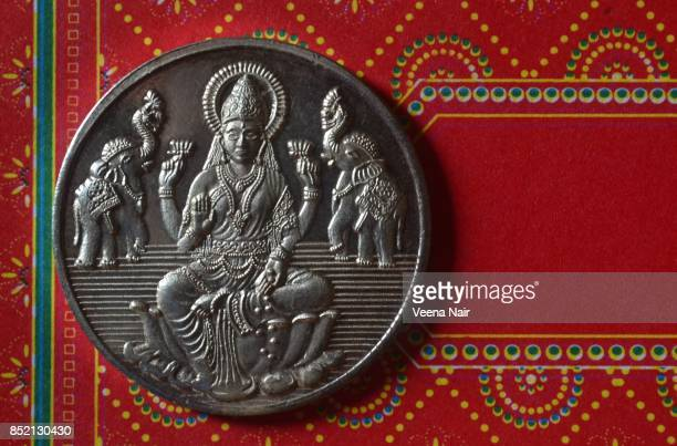 goddess lakshmi,silver coin against red, design background - goddess lakshmi stock photos and pictures