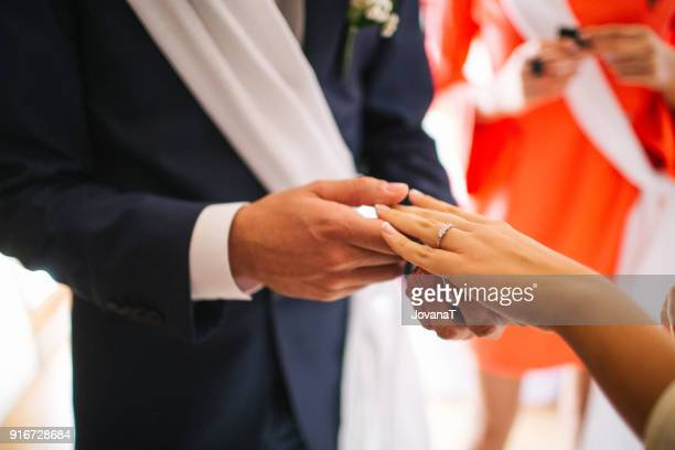 Godfather holding brides hand with wedding ring