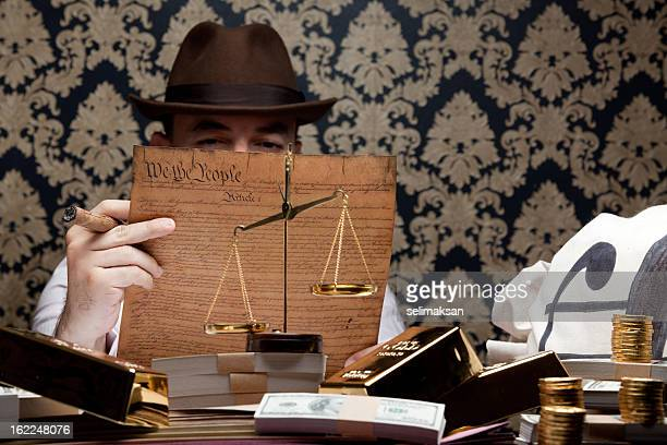 godfather holding us constitution, dirty money and golds on desk - social inequality stock pictures, royalty-free photos & images