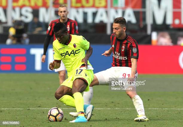 Godfred Donsah of Bologna FC is challenged by Andrea Bertolacci of AC Milan during the Serie A match between AC Milan and Bologna FC at Stadio...