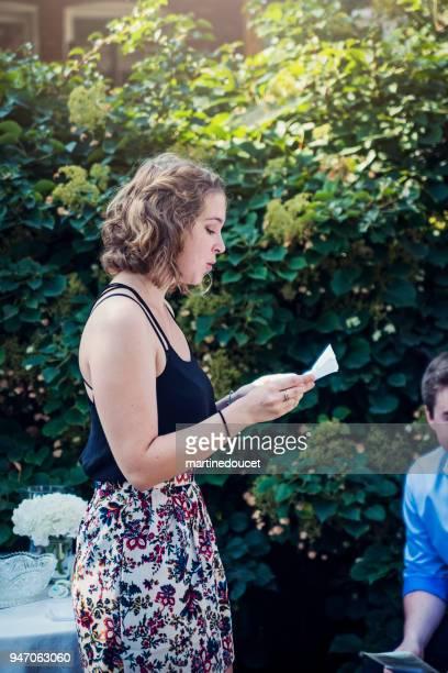 Godmother reading a prayer at outdoors baby baptism.