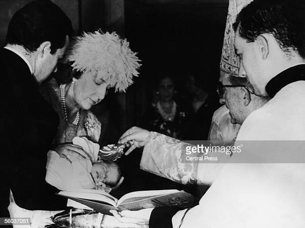Godparents Dona Cristina and Don Alfonso de Borbon Duke of Cadiz holding Princess Cristina during her christening at the Palace of Zarzuela near...
