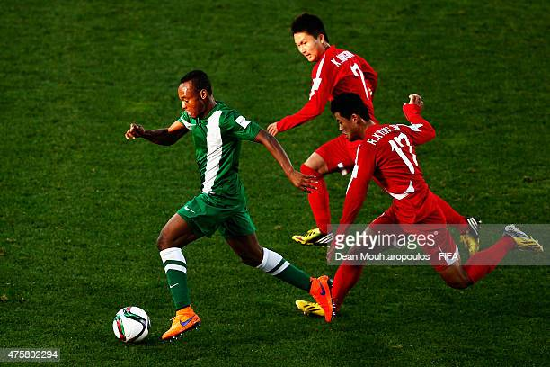 Godwin Saviour of Nigeria gets past Ri Kyong Jin and Kang Nam Gwon of Korea DPR during the FIFA U20 World Cup New Zealand 2015 Group E match between...
