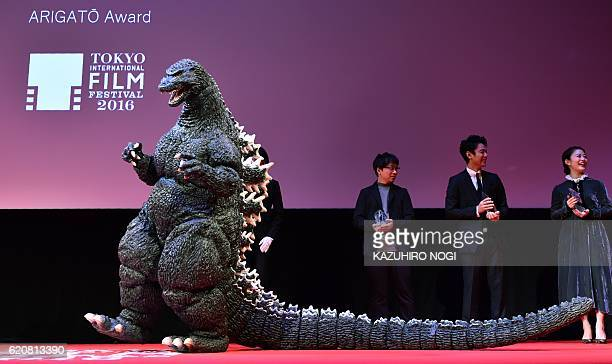 Godzilla a fictional giant monster originating from a series of its films of the same name from Japan celebrates at the award ceremony after winning...