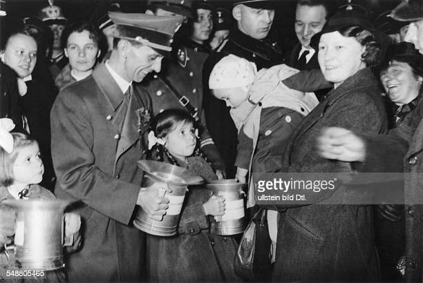 Goebbels Joseph Politician NSDAP Germany *29101897 is collecting a donation from a little girl at the 'National Day of Solidarity' in Berlin next to...