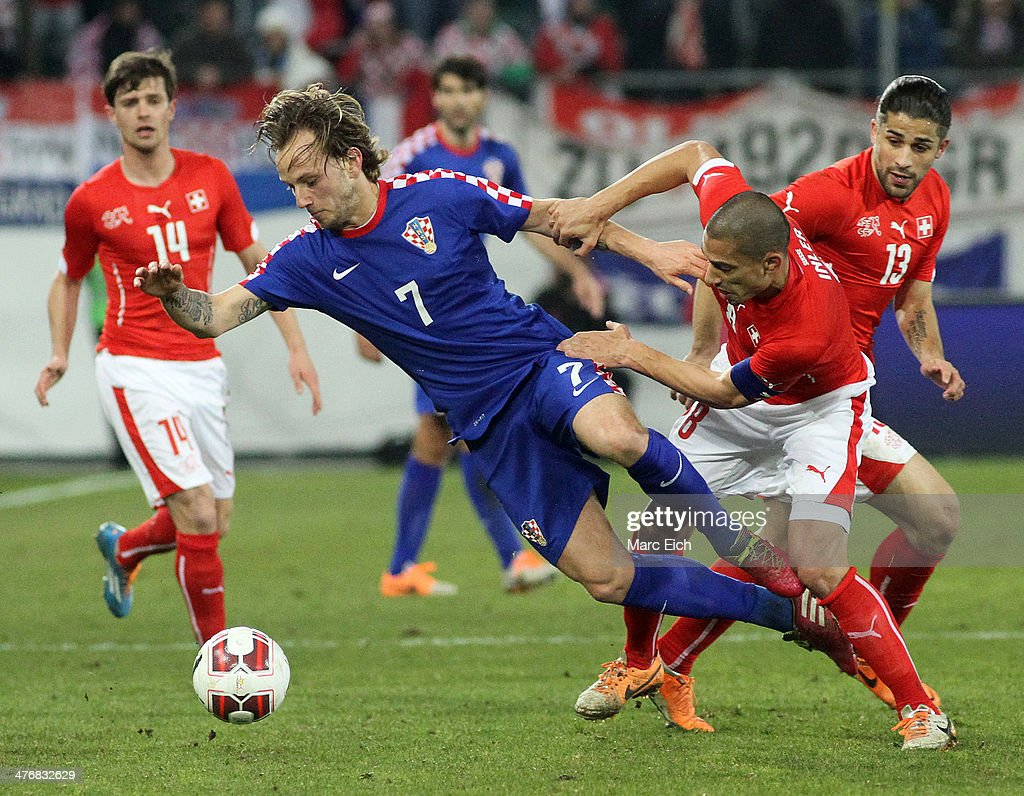 Goekhan Inler of Switzerland (R) challenges Ivan Rakitic of Croatia during the international friendly match between Switzerland and Croatia at the AFG Arena on March 5, 2014 in St Gallen, Switzerland.