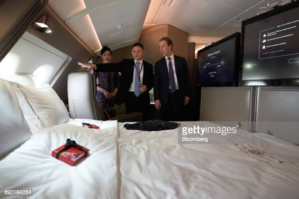 Goh Choon Phong chief executive officer of Singapore Airlines Ltd center and Fabrice Bregier chief operating officer of Airbus SE look at a suite...