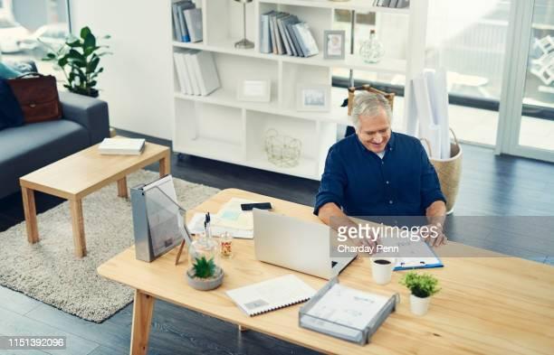 gaan door papierwerk en controleren wat de behoeften van zijn handtekening - alleen seniore mannen stockfoto's en -beelden