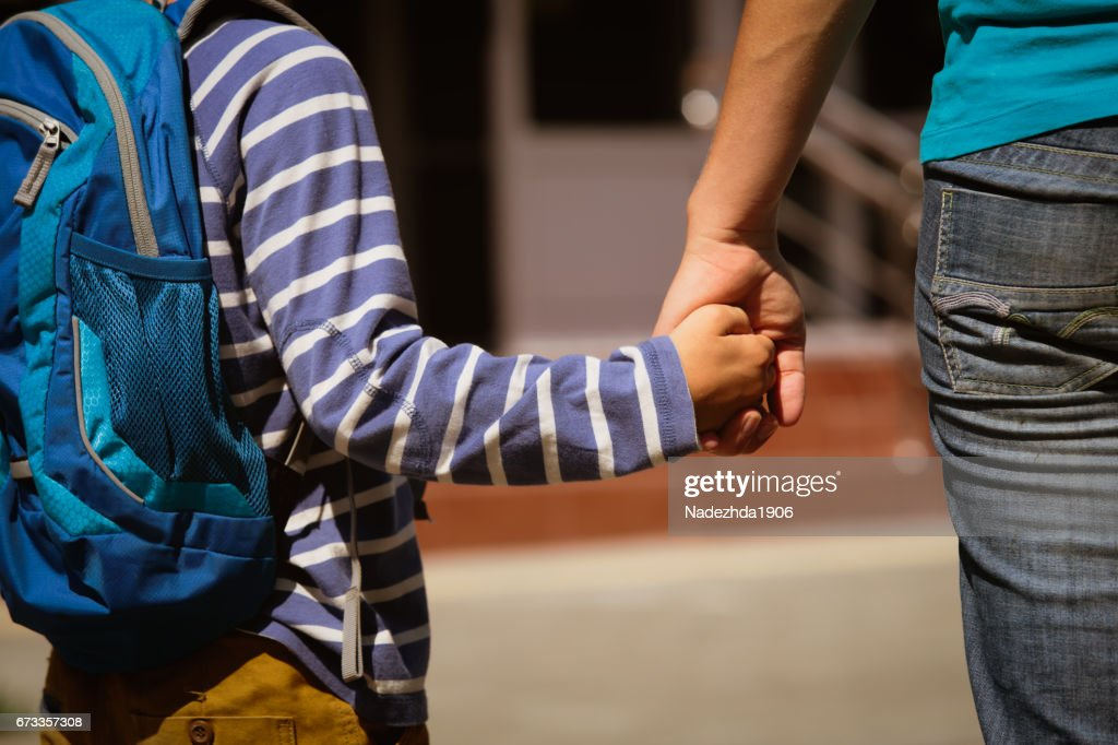 going to school- mother holding hand of son : Stock Photo