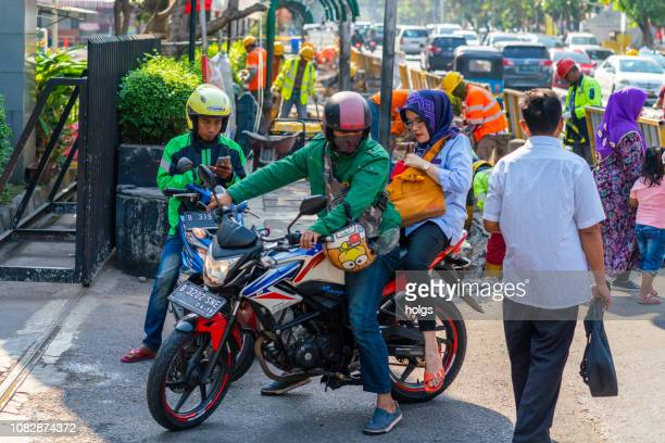 gojek motorcycle drivers with passenger in jakarta, indonesia - java stock pictures, royalty-free photos & images