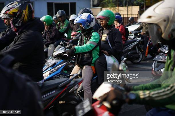 A GoJek motorcycle taxi driver and a passenger sit in traffic in Jakarta Indonesia on Saturday Aug 4 2018 Indonesia'sgig economy is booming yet...