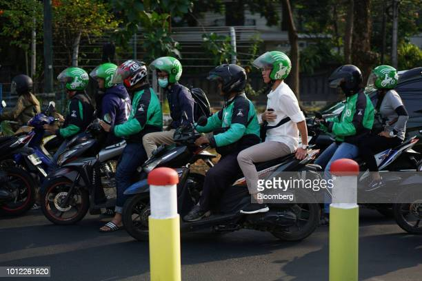 GoJek motorcycle taxi drivers and passengers sit in traffic in Jakarta Indonesia on Saturday Aug 4 2018 Indonesia'sgig economy is booming yet...