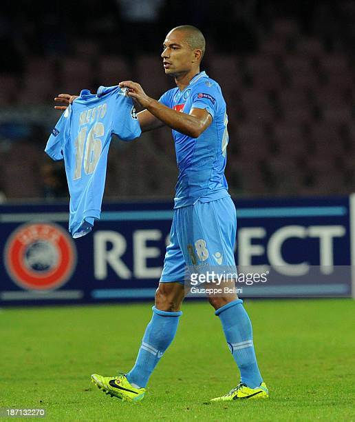 Gokhan Inler of Napoli celebrates with the shirt of his injured teammate Giandomenico Mesto after scoring their first goal during the UEFA Champions...
