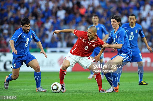 Gokhan Inler of Switzerland is challenged by Gennaro Gattuso and Riccardo Montolivo of Italy during the international friendly match between...