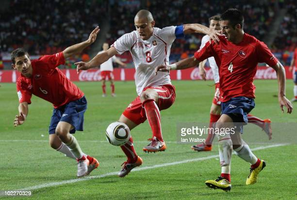 Gokhan Inler of Switzerland is closed down by Carlos Carmona and Mauricio Isla of Chile during the 2010 FIFA World Cup South Africa Group H match...