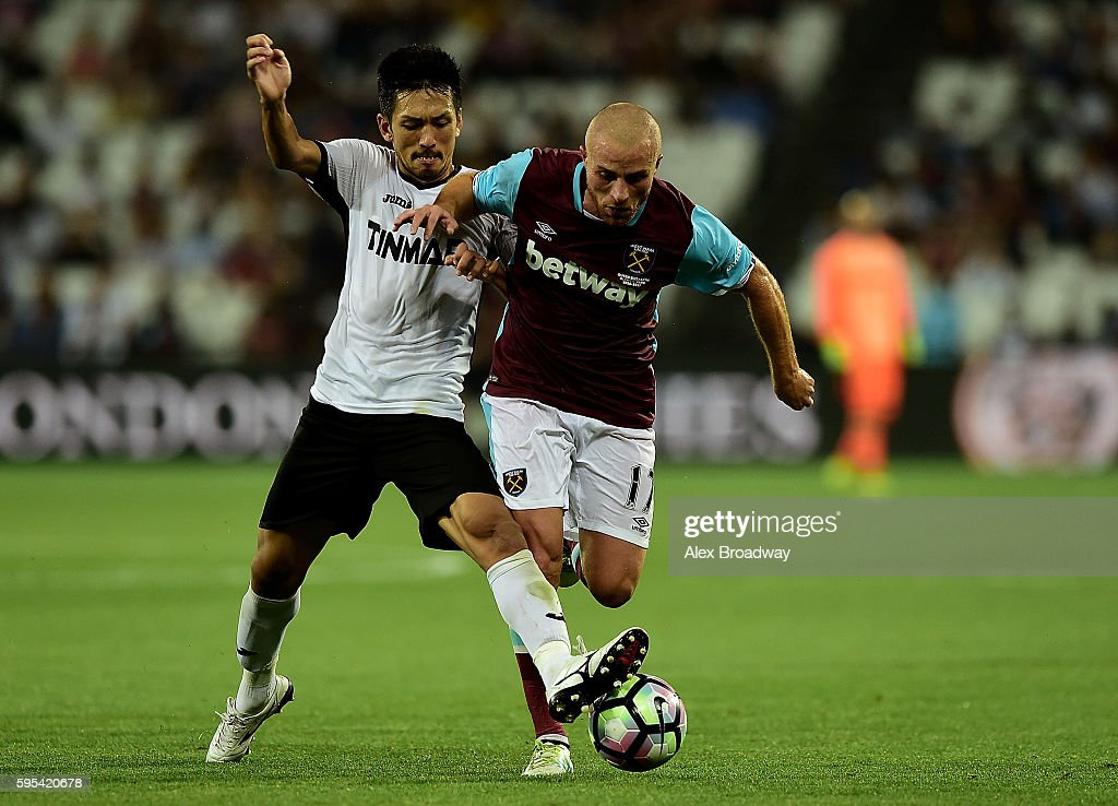 Gokhan Tore of West Ham holds off pressure from Takayuki Seto of FC Astra Giurgiu during the UEFA Europa League match between West Ham United and FC Astra Giurgiu at the Olympic Stadium on August 27, 2016 in London, England.