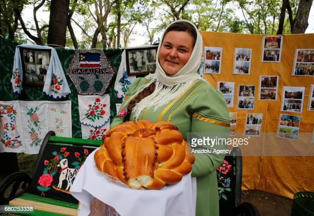 Gokoguz Christian Turk woman, wearing traditional clothes, shows a bread during the Hidirellez celebrations at Stefan Cel Mare Central Park in...
