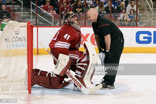 Golatender Mike Smith of the Arizona Coyotes talks with Coyotes head athletic trainer Jason Serbus during a timeout against the St Louis Blues at...