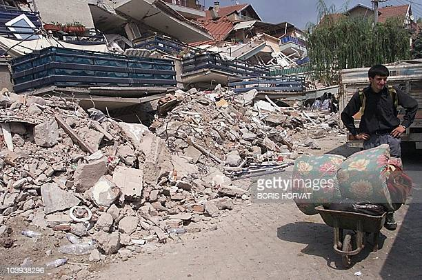 A Golcuk resident carries his last belongings in a wheel barrow 20 August 1999 in a Golcuk street some 15 km from Izmit The death toll in the 17...