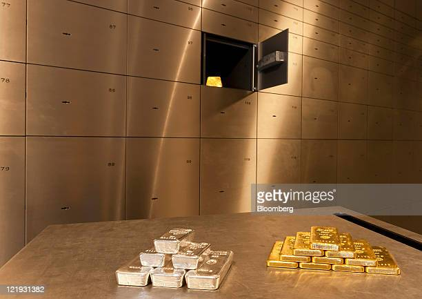 Gold and silver bars sit in piles on a table in the vault of gold vendor ProAurum in Munich Germany on Tuesday Aug 23 2011 Gold advanced to an...