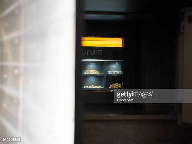 Gold and silver bars sit inside an illuminated bulletproof glass display case inside Pro Aurum KG in Munich Germany on Tuesday Jan 30 2018 Gold...
