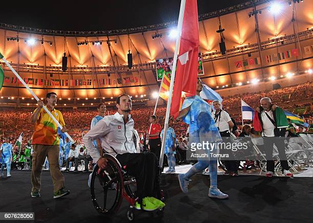 Gold and silver medalist Marcel Hug carries the flag for Switzerland during the closing ceremony of the Rio 2016 Paralympic Games at Maracana Stadium...