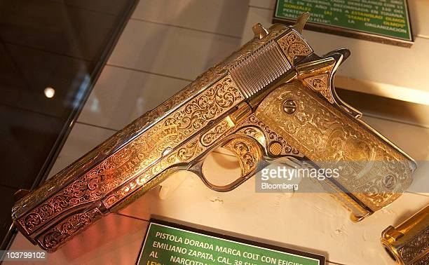 A gold and silver plated Colt pistol seized from a drug smuggler sits on display at the Mexican Secretary of National Defense headquarters building...