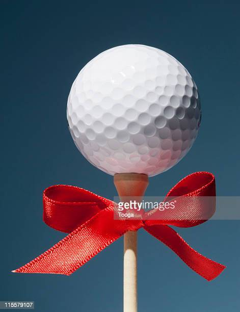 Gold ball on tee with red bow