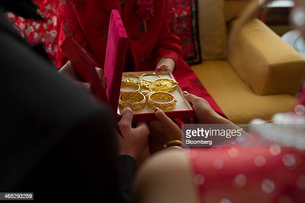 Gold bangles are presented as a gift to a bride during the tea ceremony of her wedding in Hong Kong China on Saturday Jan 25 2014 Hedge funds got...