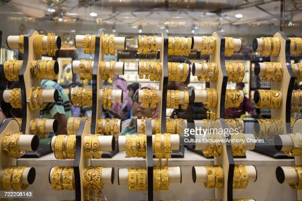gold bangles in shop window at the gold souk, deira, dubai, united arab emirates - bangle stock pictures, royalty-free photos & images