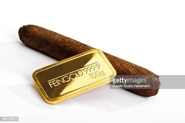 Gold bar and cigar against white background, close-up