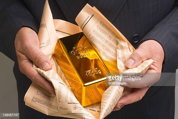 Gold bar wrapped in a financial newspaper